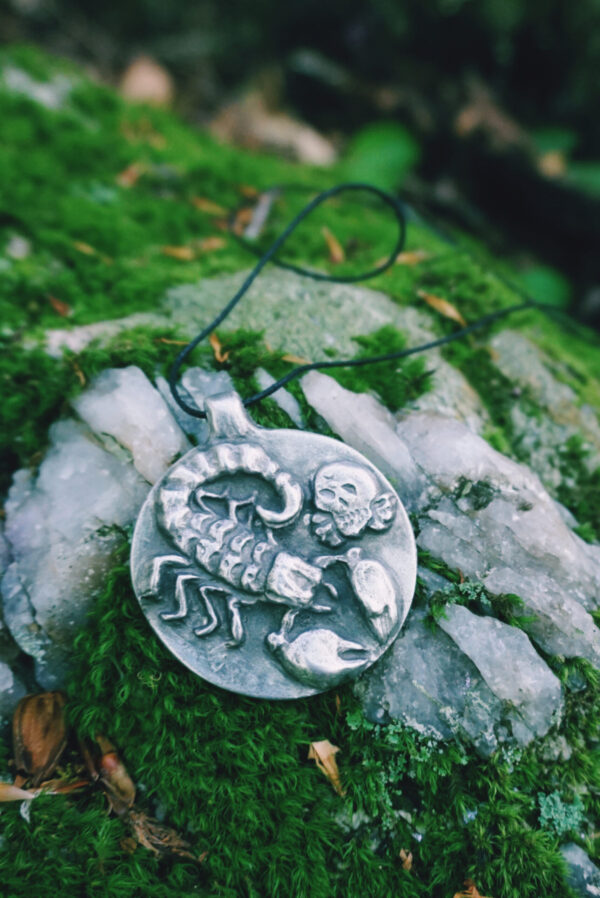 An ancient mars amulet used occult art rests on a mossy rock.